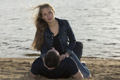 Young couple lying on the sandy beach Royalty Free Stock Images