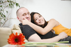 Young couple lying on sofa Stock Photos