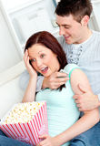 Young couple lying on sofa with popcorn and remote Stock Photography