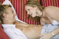 Young couple lying on sofa together side view Stock Photos