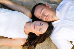 Young couple lying on a stone floor with eyes closed Royalty Free Stock Photography