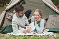 Young couple lying in tent with a map Stock Photo