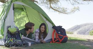 Young couple lying in tent. Two young tourists lying in tent under tree shadows and having conversation after trekking in mountains stock footage