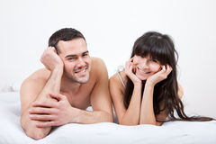 Young couple lying up in bed Royalty Free Stock Images