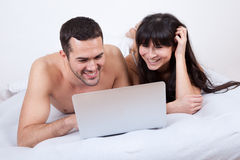 Young couple lying up in bed with laptop Royalty Free Stock Image