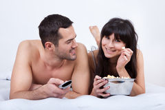 Young couple lying up in bed and watching TV Stock Image