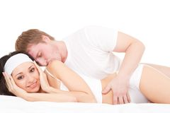 Young couple lying on the white bed Royalty Free Stock Image