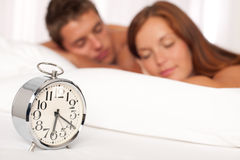 Young couple lying in white bed with alarm clock Royalty Free Stock Photo