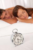 Young couple lying in white bed with alarm clock Royalty Free Stock Images