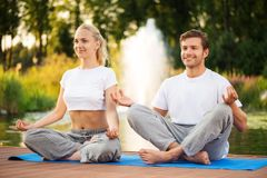 Young couple maditating in lotus pose Royalty Free Stock Image