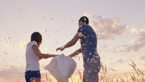 Young couple are madly having fun. A woman is beating her pillow with a friend, feathers are flying. Fight against the stock video footage