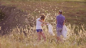 Young couple are madly having fun. A woman is beating her pillow with a friend, feathers are flying. Fight against the stock footage