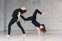 Young couple make acrobatic element. Royalty Free Stock Image
