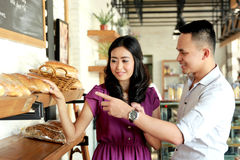 Young couple make a choice to bread they will buy Stock Images