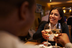 Young couple make a toast at restaurant, over-shoulder view Stock Images