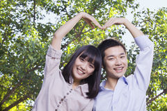 Young Couple Making a Heart Shape with Their Arms Royalty Free Stock Image