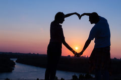 Young couple making heart shape with their hands at sunset. Silhouette of young couple making heart shape with hands on hill above the city at sunset Royalty Free Stock Photos
