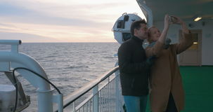Young couple making phone selfie on shipboard. Young man and woman taking selfie with smart phone on the deck while traveling by ship. Tourists making picture on stock video