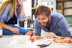 Young Couple Making Pizza In Kitchen Together Royalty Free Stock Images