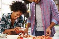 Young Couple Making Pizza In Kitchen Together Stock Photo