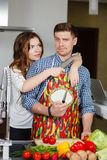 Young couple making a salad together in the kitchen Stock Photos
