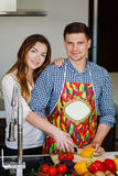 Young couple making a salad together in the kitchen Royalty Free Stock Photography