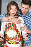 Young couple making a salad together in the kitchen Royalty Free Stock Images
