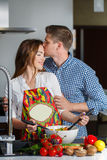 Young couple making a salad together in the kitchen Stock Image