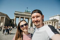 Young couple making selfie against the background of the Brandenburg Gate in Berlin. Young beautiful couple making selfie against the background of the royalty free stock photography