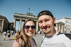 Young couple making selfie against the background of the Brandenburg Gate in Berlin. Young beautiful couple making selfie against the background of the stock image