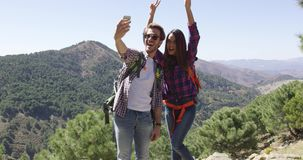 Young couple making selfie while hiking. Two young smiling people taking selfie while hiking in mountains in summer time stock video