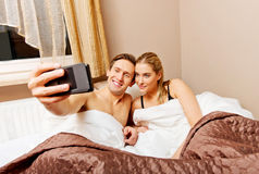Young couple making selfie while lying in bed Royalty Free Stock Photos
