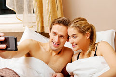 Young couple making selfie while lying in bed Royalty Free Stock Photography