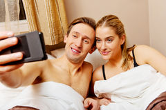 Young couple making selfie while lying in bed Stock Image