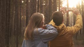 Young man and woman make photo at phone in forest. Young couple making selfie at smartphone at background of sunny green forest. Hiking emotionally concept of stock footage