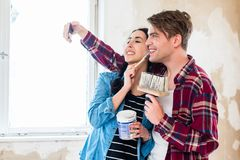 Young couple making a selfie while working to the renovation of their home stock photo