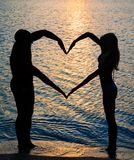 Young couple making shape of heart with arms on beach. Young couple making heart shape with arms on beach against golden sunset Royalty Free Stock Photo