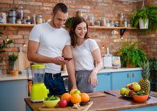 Young couple making smoothie in kitchen stock photo