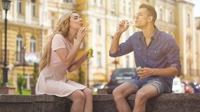 Young couple making soap bubbles, playful romantic mood on date, freedom Stock Photo