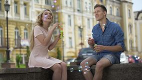 Young couple making soap bubbles, reaching each other to kiss, playfulness stock video footage