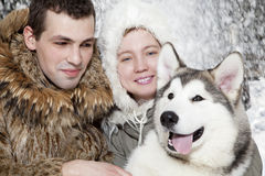 Young couple with a malamute dog Royalty Free Stock Photo