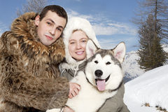 Young couple with a malamute puppy Royalty Free Stock Photography