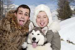 Young couple with a malamute puppy Stock Photos