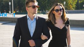 Young couple of male and female business people walking in the city street. Portrait of businessman and businesswoman stock footage