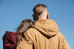 Young couple. Young male hugging female  rear view blue sky on background Royalty Free Stock Image