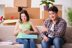 The young couple of man and pregnant wife with giftbox. Young couple of men and pregnant wife with giftbox Royalty Free Stock Images