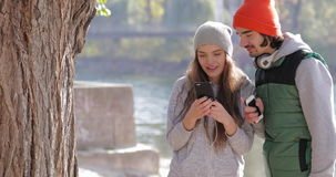 Young Couple Man And Pretty Woman Using Cell Smart Phone Outdoor Sunrise, Morning Autumn Park stock video