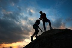 Young couple man and woman climbing on boulder. Helping hand. Silhouettes on sunset background. stock photos