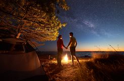 Young couple man and woman having rest at tourist tent and burning campfire on sea shore near forest. Night camping at lake under blue starry sky. Back view of royalty free stock image