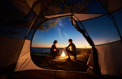 Young couple man and woman having rest at tourist tent and burning campfire on sea shore near forest stock image